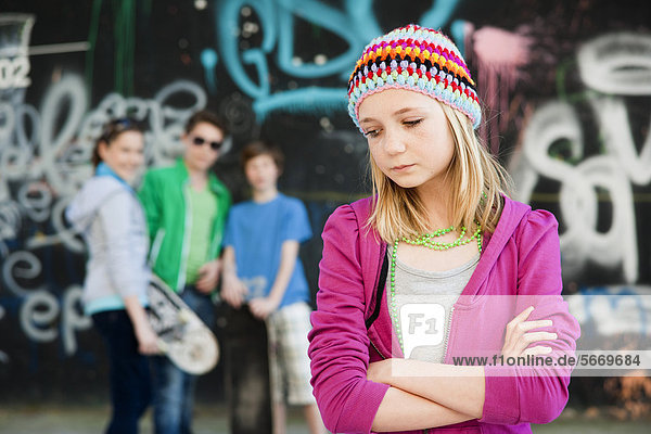 Traurige Teenagerin mit drei Teenagern im Hintergrund
