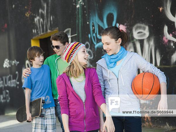 Vier fröhliche Teenager-Freunde gehen an einer Graffitiwand