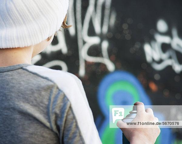 Teenager mit einer Spraydose vor Graffitiwand