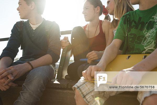 Vier Teenager-Freunde sitzen mit Mappen im Freien