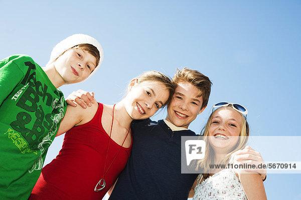 Vier fröhliche Teenager-Freunde im Freien