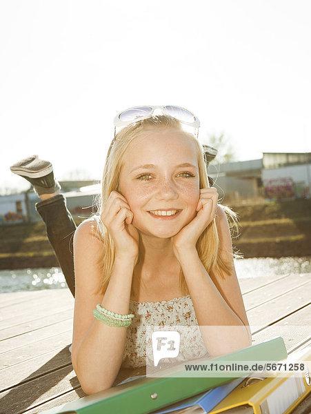 Lächelnde Teenagerin liegt auf einem Steg