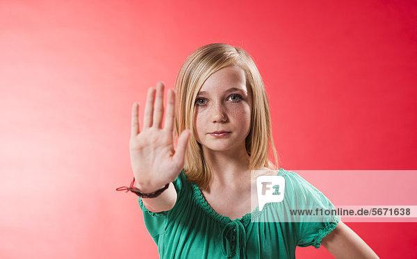 Teenagerin hebt ihre Hand zur Abwehr
