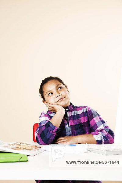 Mädchen mit Hausaufgaben am Tisch schaut nach oben