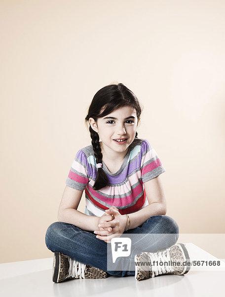 Lächelndes Mädchen sitzt auf dem Tisch
