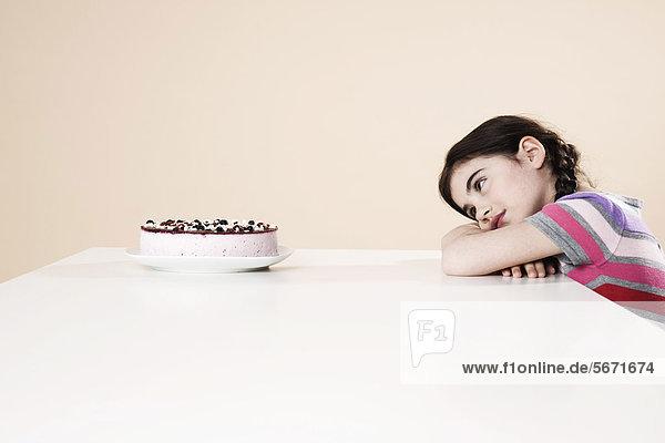 Mädchen sitzt am Tisch mit einer Sahnetorte