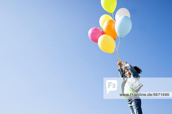 Mädchen steht mit Luftballons unter blauem Himmel
