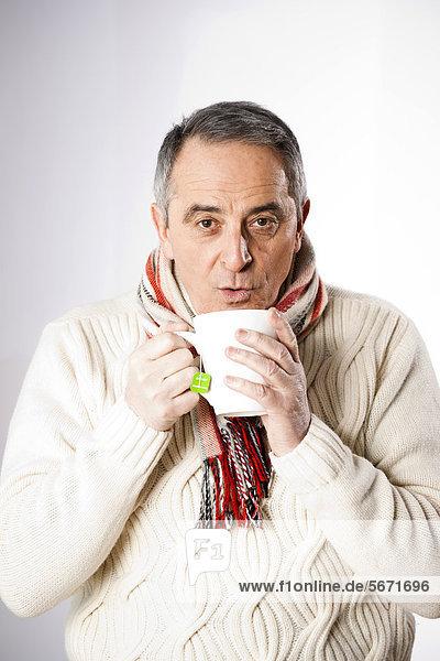 Senior in Winterkleidung trinkt eine Tasse Tee