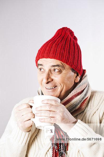 Fröhlicher Senior in Winterkleidung trinkt eine Tasse Tee