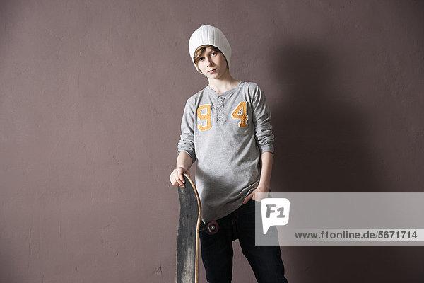 Teenager mit Wollmütze hält ein Skateboard