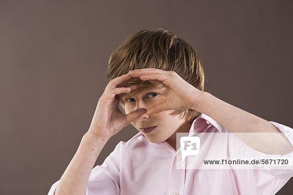 Teenager schaut durch seine Hände