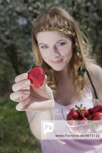 Blonde Frau hält Erdbeeren in der Hand
