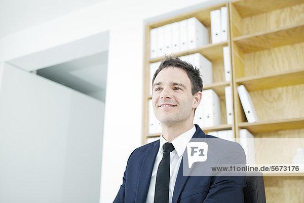 Lächelnder Geschäftsmann im Büro denkt nach