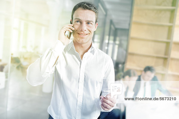 Lächelnder Geschäftsmann im Büro telefoniert