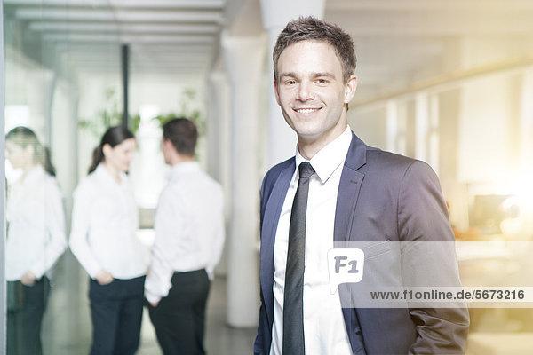 Lächelnder Geschäftsmann mit Geschäftsleuten im Büro