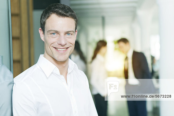Smiling businessman with business people in office