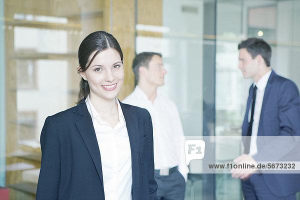 Lächelnde Geschäftsfrau mit Geschäftsmännern im Büro