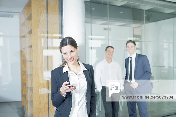 Smiling businesswoman with businessmen in office