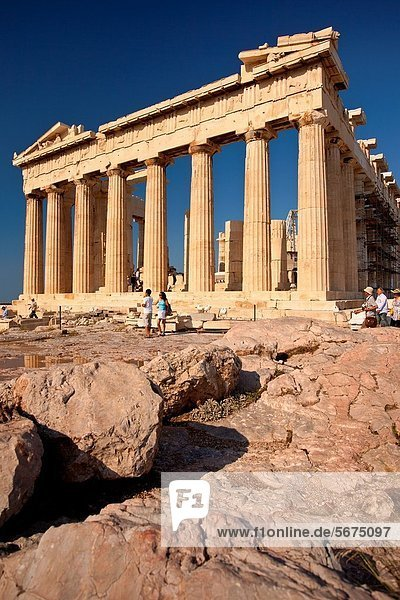 Tourists walk past the marble ruins of the Parthenon on the Acropolis, Athens Attica Greece Y9R-1699573