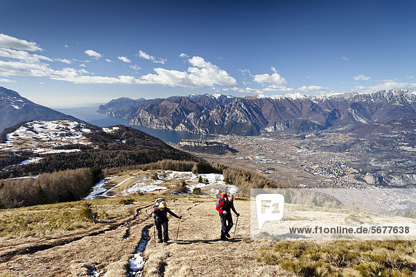 Wanderer beim Aufstieg zum Monte Stivo oberhalb von St. Barbara am Gardasee  hinten der Gardasee mit dem Dorf Riva  unten das Dorf Arco  Trentino  Italien  Europa