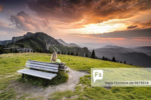Frau sitzt auf einer Holzbank und genießt den Blick vom Brauneckgipfel  Bayern  Deutschland  Europa