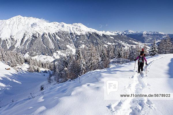 Schneeschuhwanderer beim Aufstieg zur Jagelealm im Ridnauntal oberhalb von Entholz  hinten der Rosskopf und die Telfer Weißen  unten das Ridnauntal  Südtirol  Italien  Europa