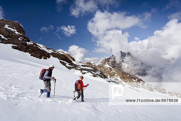 Wanderer beim Abstieg von der Lorcherspitz auf dem Weißbrunnferner oberhalb des Grünsees  hinten die Weißbrunnspitz und Zufrittspitz im Hochnebel  Südtirol  Italien  Europa