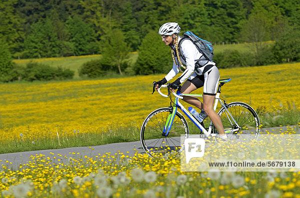 Junge Frau fährt Rennrad  Oberbayern  Bayern  Deutschland  Europa