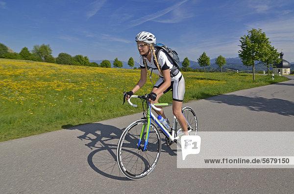 Young woman riding a racing bike  Upper Bavaria  Bavaria  Germany  Europe