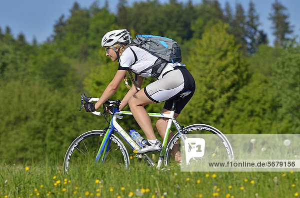 Young woman riding a racing cycle  Upper Bavaria  Bavaria  Germany  Europe