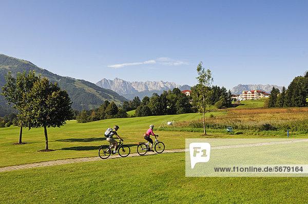 Paar mit Elektrofahrrädern vor dem Golfhotel Peternhof  zwischen Reit im Winkl  Chiemgau  Oberbayern  Bayern  Deutschland  und Kössen  Tirol  Österreich  Europa