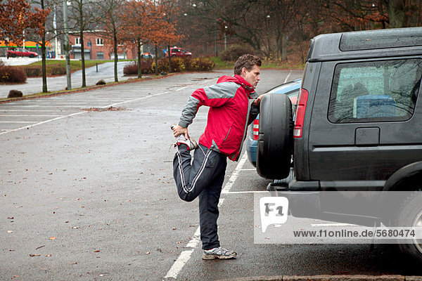 Mature man stretching against car in car park