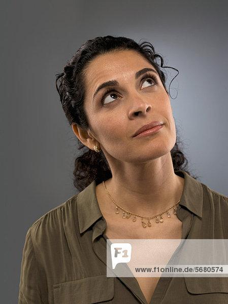 Mittlere erwachsene Frau schaut nach oben  Studioaufnahme