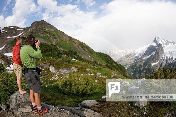 Photographing rainbow in mountains  White Rock Lakes  Ptarmigan Traverse  North Cascades  Washington  USA