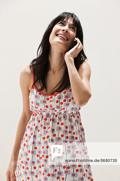 Lächelnde reife Frau mit Handy  Studioaufnahme