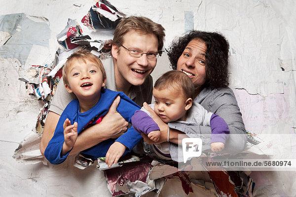 Glückliche Familie  die durch eine Wand bricht.