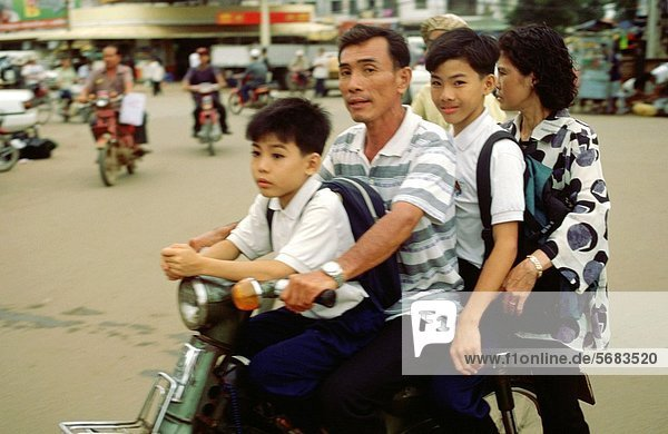 A man with his two children and his wife on their motorbike in Hanoi Vietnam is one fo the few places where motorbikes dominate the city streets - and occasionally 4 to 5 peopel can pile onto a bike