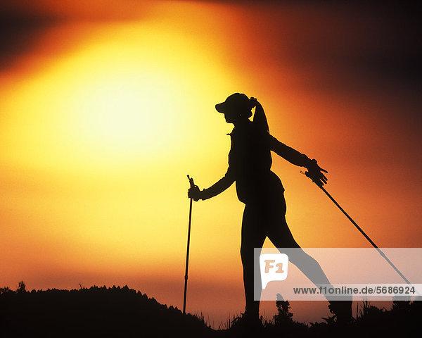 Frau macht Nordic Walking bei Sonnenuntergang  Söll  Österreich