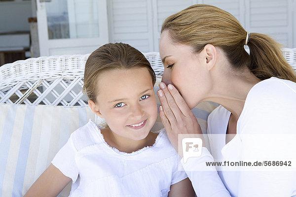 Frau flüstert der lächelnden Tochter zu.
