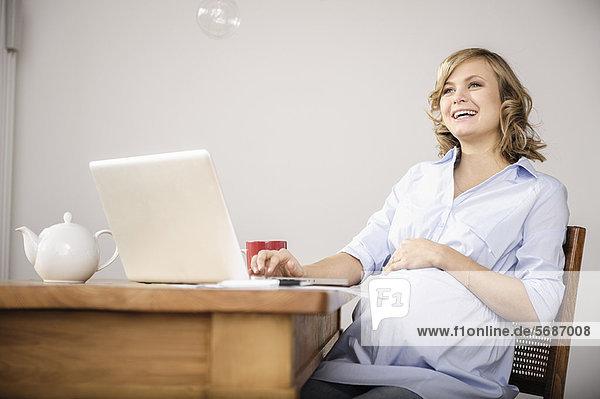 Schwangere Frau mit Laptop in der Küche