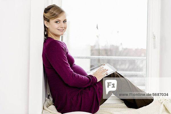 Schwangere Frau im Fenster sitzend