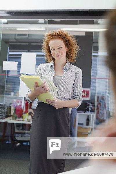 Geschäftsfrau mit Mappe im Büro