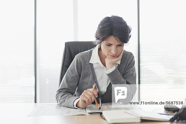 Businesswoman reading newspaper at desk