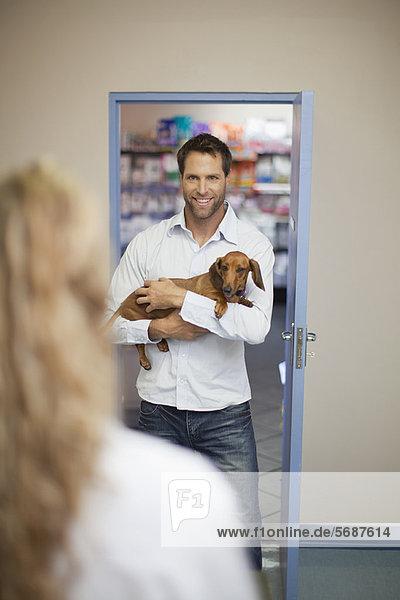 Mann bringt Hund zum Tierarzt
