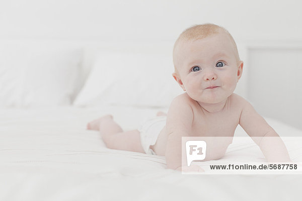 Smiling baby laying on bed