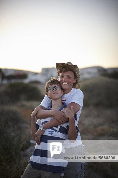 Außenaufnahme  umarmen  lächeln  Bruder  freie Natur