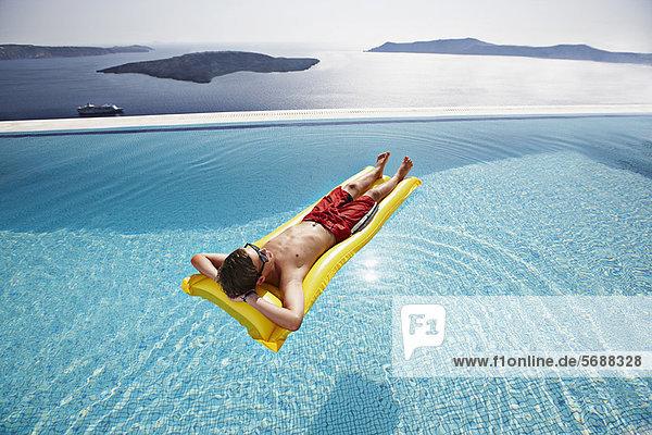 Teenager-Junge entspannt auf dem Floß im Pool