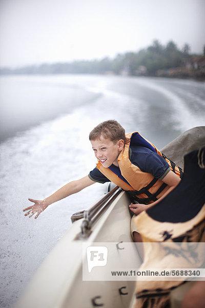 Teenager-Junge  der vom Boot aus zum Wasser greift