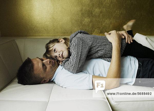 Vater und Tochter entspannen sich auf dem Sofa