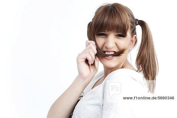 Junge Frau hält sich Haarzopf zwischen Zähne und lacht
